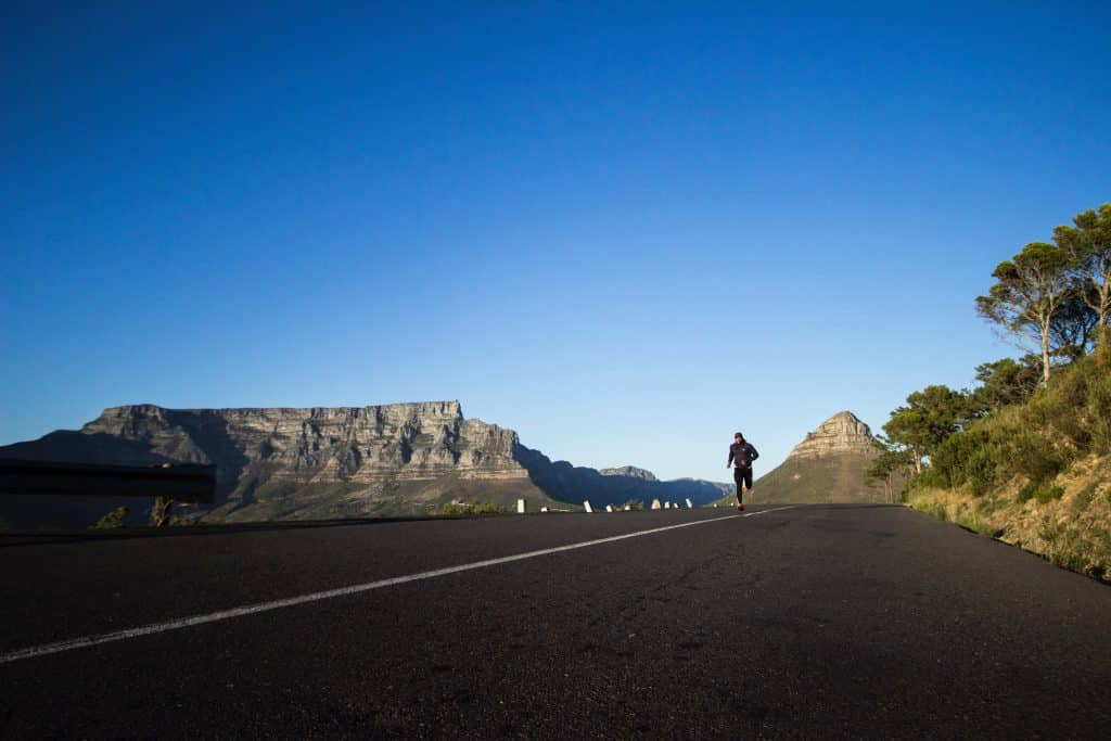 Homem correndo em uma estrada