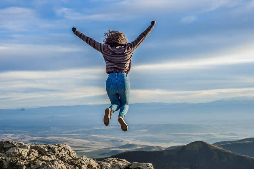 Mulher no topo da montanha pulando com os braços para cima
