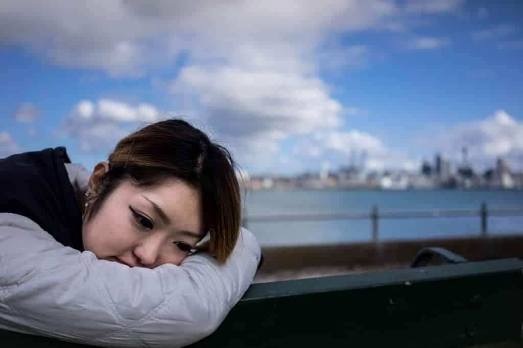 Imagem de fundo de um lindo lago e em destaque uma mulher japonesa sentada em um banco de madeira. Ela usa uma jaqueta de frio na cor cinza com capuz preto. Ela está com a cabeça debruçada no braço e meio se sentindo culpada por ter feito algo.
