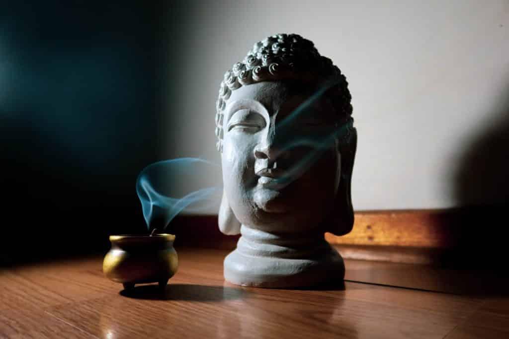 Imagem de  um incensário e dentro dele um incenso aceso. Ao lado a estátua da cabeça de Buda.