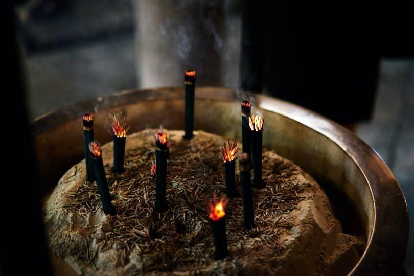Imagem de um grande incensário e sobre ele vários incensos acesos.
