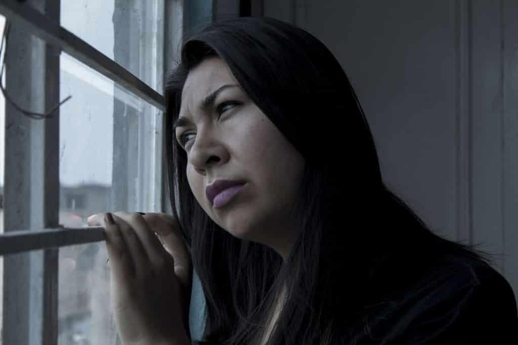 Imagem de uma mulher triste olhando pela janela. ELa está com a cabeça encostada na janela. Está se sentindo culpada por ter feito algo. Ela usa cabelos longos.