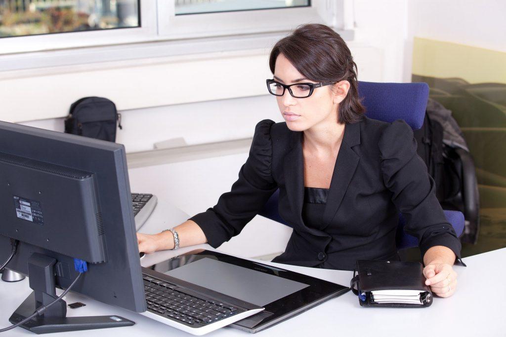 Imagem de uma secretária trabalhando em seu escritório. Ela está sentada em sua cadeira de frente para o seu computador. Usa um terno preto, cabelos curtos e presos e um óculos de grau com armação na cor preta.