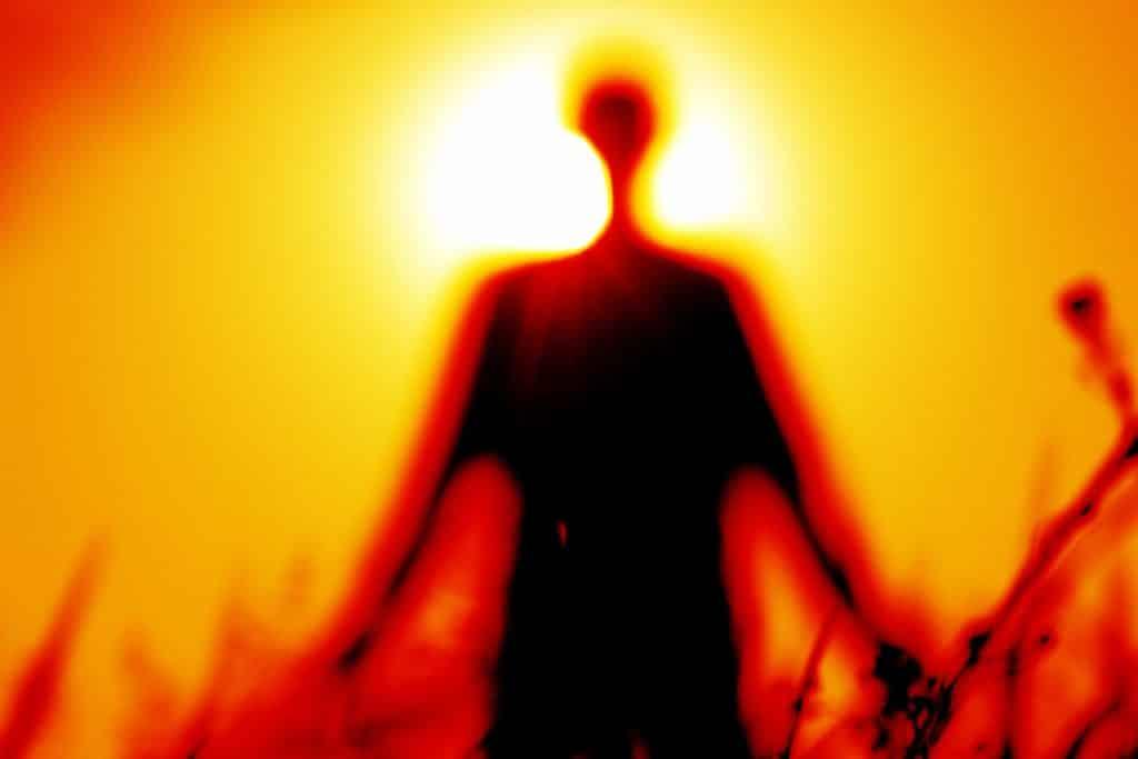 Imagem de fundo avermelhada, representando a energia solar e em destaque a silhueta de uma pessoa, representando a espiritualidade.