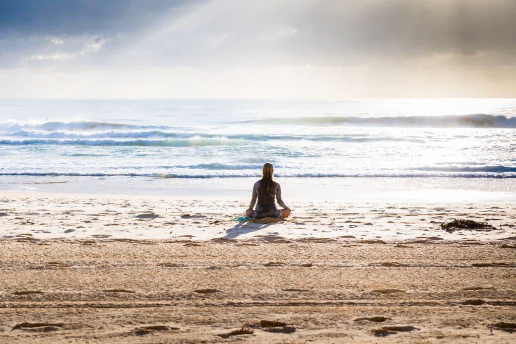 Mulher branca meditando na praia.