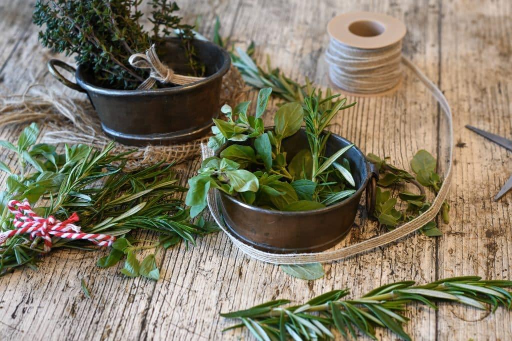 Imagem de vários tipos de ervas dispostos em potes de alumínio e também sobre uma mesa de madeira de fundo branco. Eles estão sendo separados para o preparo de um banho aromático.