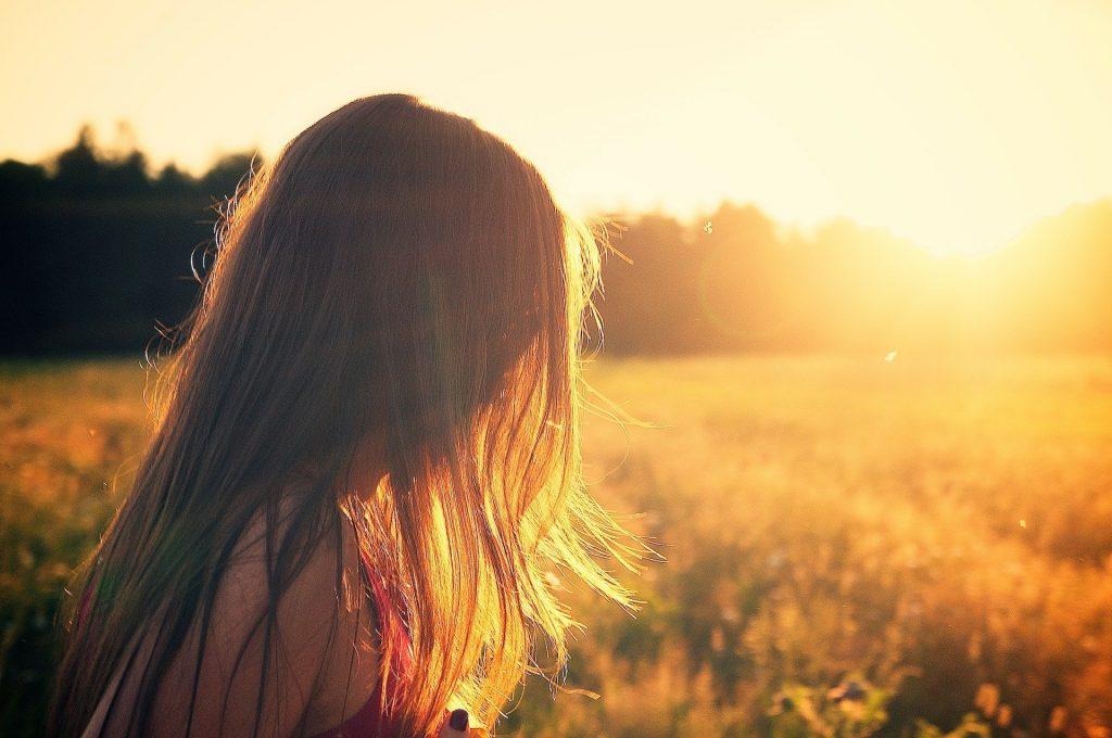 Imagem de um lindo pôr do sol ao fundo e em destaque o rosto de uma mulher de perfil, coberto por seus longos cabelos. A luz do sol reflete sobre os fios, deixando-os mais claros.