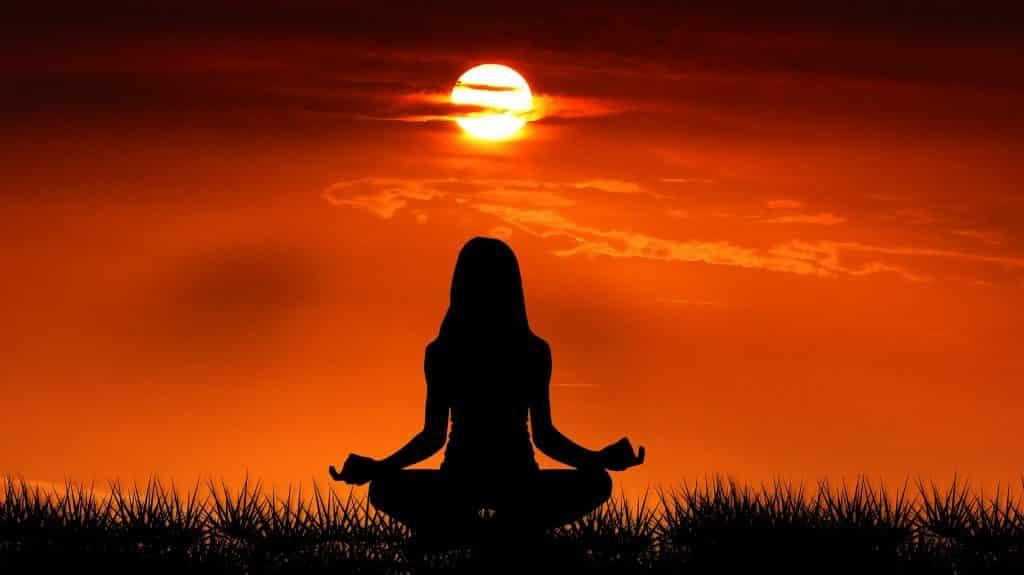 Imagem de fundo avermelhada de um lindo nascer do sol. Em Destaque a silhueta de uma moça sentada de frente para ele, praticando meditação.