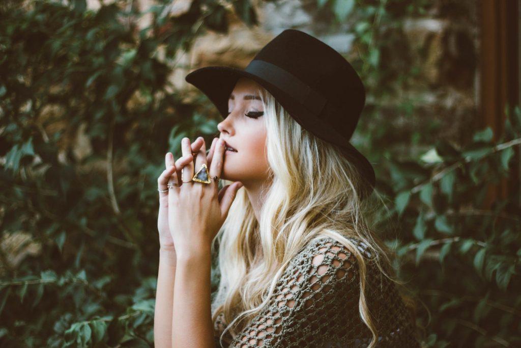 Imagem de uma jovem mulher loira de cabelos longos. Ela usa um chapéu preto e alguns aneis nos dedos. Está com os olhos fechados e as duas mãos sobre os lábios. Ela está pensativa, mas com um rosto leve e feliz.