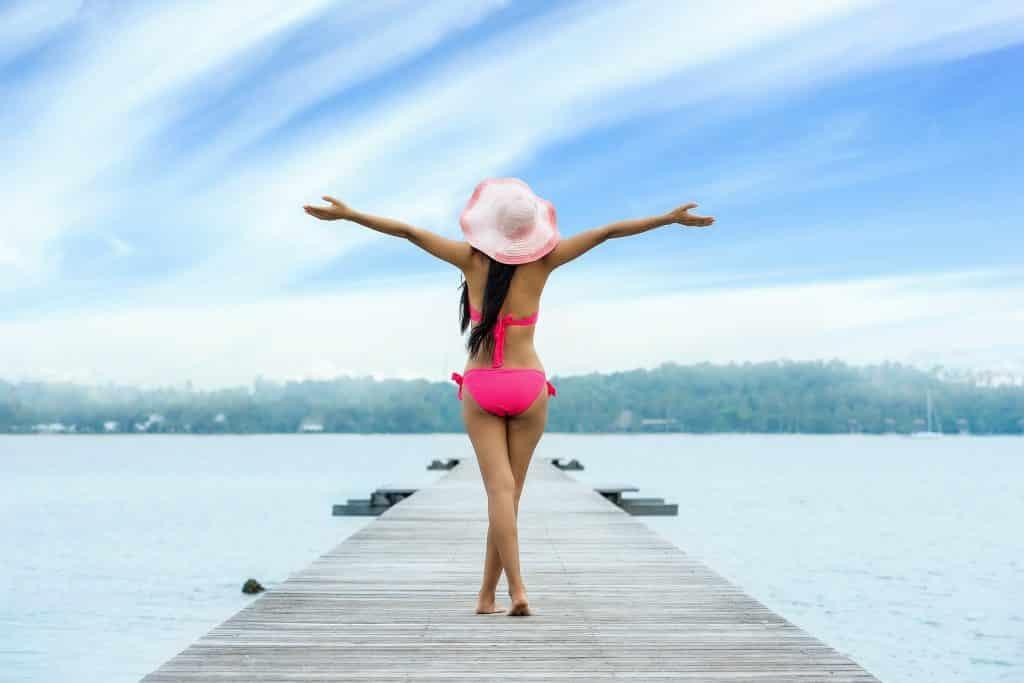 Imagem de uma mulher usando um biquíni rosa e um chapéu na cor rosa. Ela está caminhando sobre um píer próximo a um grande lago. Ela está tendo uma sensação de liberdade, pois está com os braços abertos, respirando um ar puro.