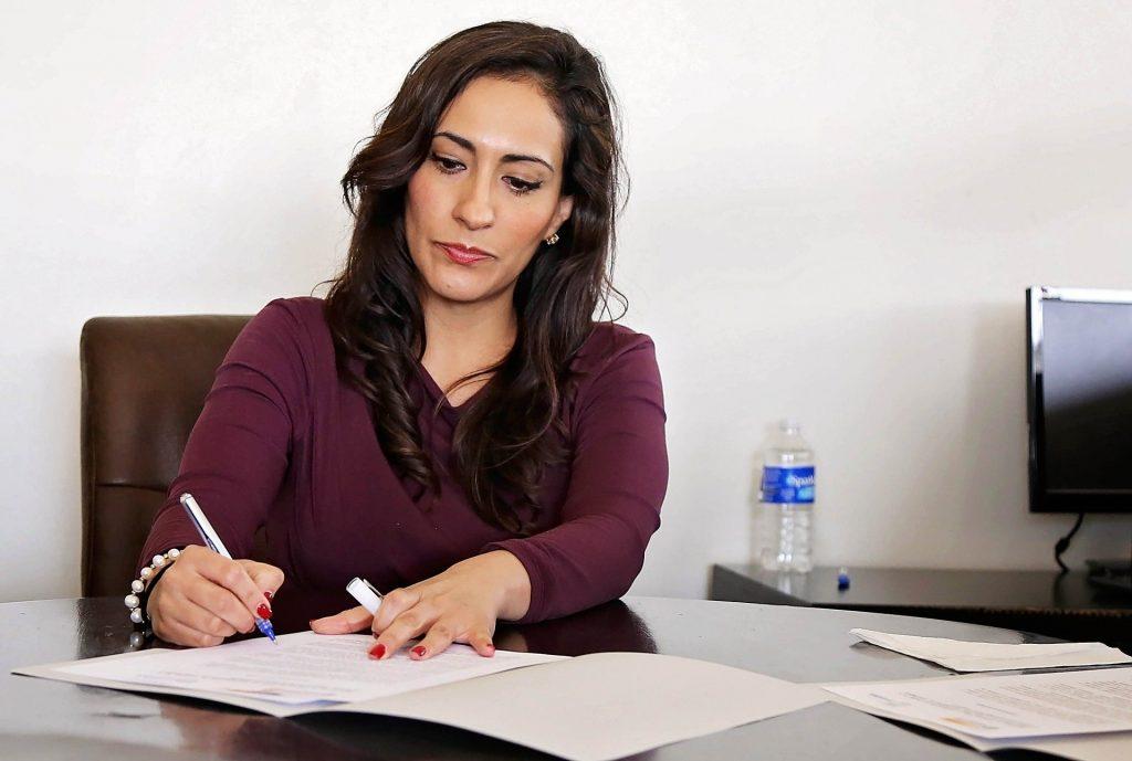 Imagem de uma mulher de cabelos longos e castanhos, sentada em uma cadeira de escritório. Ela está assinando alguns documentos. Ao fundo uma mesa com uma TV e uma garrafa com água.