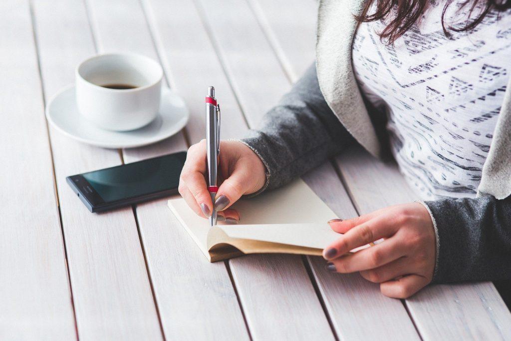 Imagem de uma mulher sentada em frente a uma mesa de madeira na cor branca. Ela usa um casado de moleton na cor cinza. Ela está escrevendo à caneta em uma agenda e ao lado dela uma xícara branca sobre um pires branco contendo café e um celular.