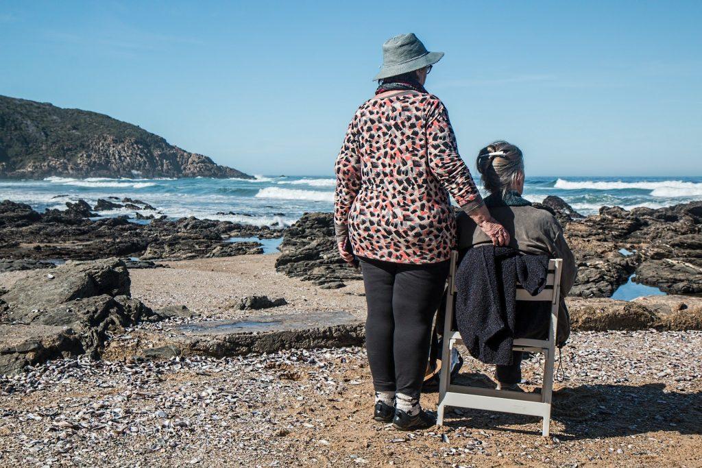 Imagem de duas amigas em uma praia. Uma está sentada em uma cadeira de madeira e a outra está em pé, apoiando a outra. Ambas olham para as águas e ondas do mar.