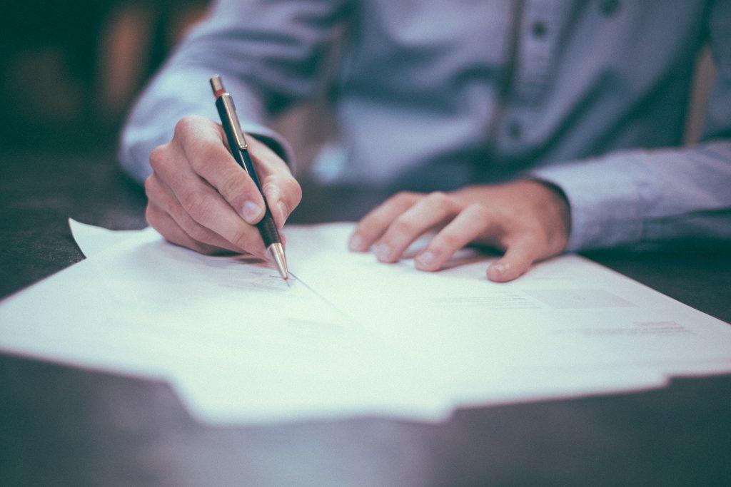 Imagem de um homem vestindo uma camisa cinza-claro. Ele está sentado e escrevendo em alguns papéis dispostos sobre a sua mesa.