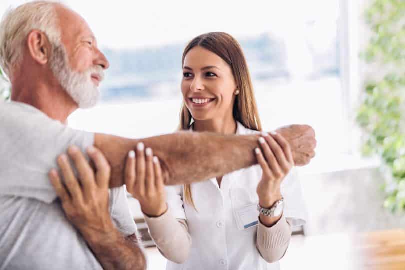 Doutora segurando braço de paciente