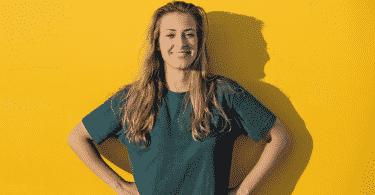 Mulher sorrindo confiante com as mãos na cintura em fundo amarelo