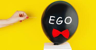 """Balão escrito """"ego"""" prestes a ser furado por um palito de dente"""