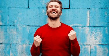 Homem contente comemorando com os punhos fechados