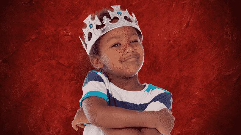 Criança usando coroa de rei com os braços cruzados