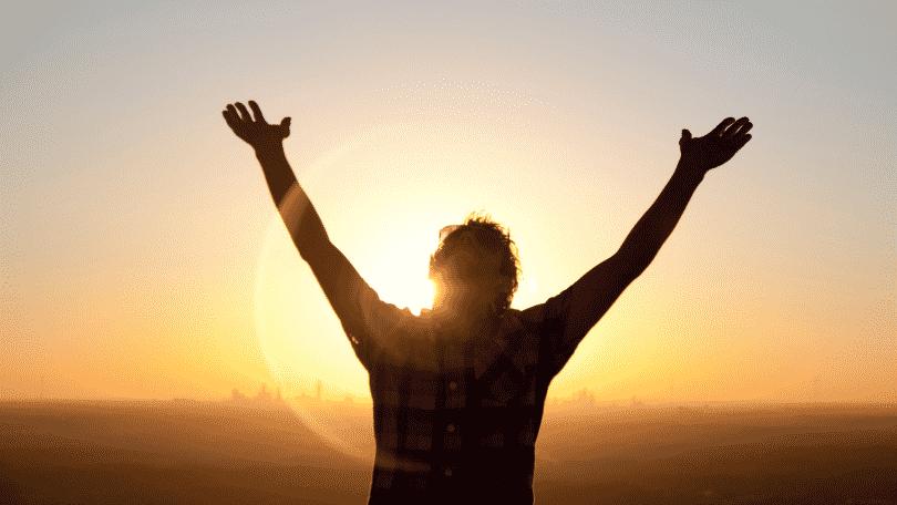 Homem com os braços erguidos vendo o por do sol