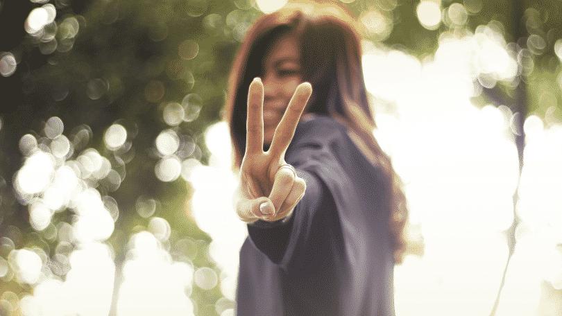 """Mulher fazendo um """"v"""" com os dedos sorrindo"""