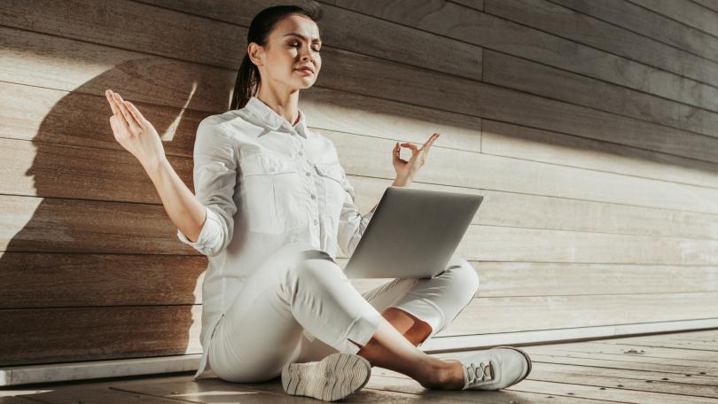 Mulher meditando com um laptop no colo