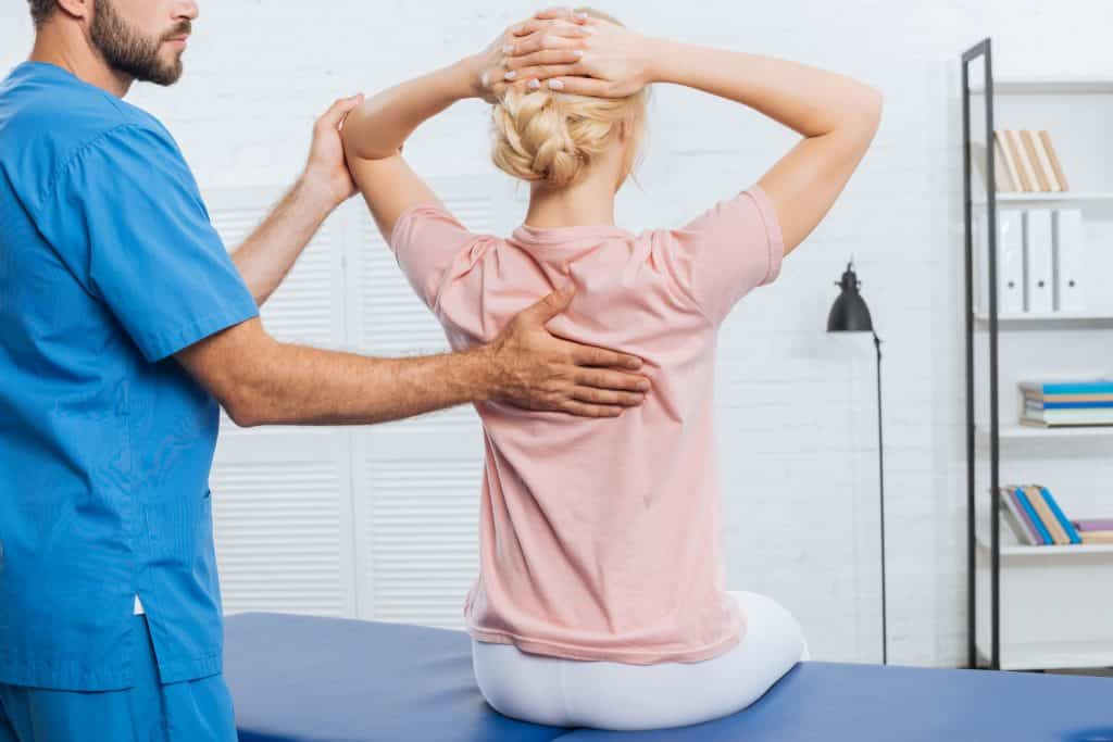 Fisio terapista com as mãos nas costas da paciente