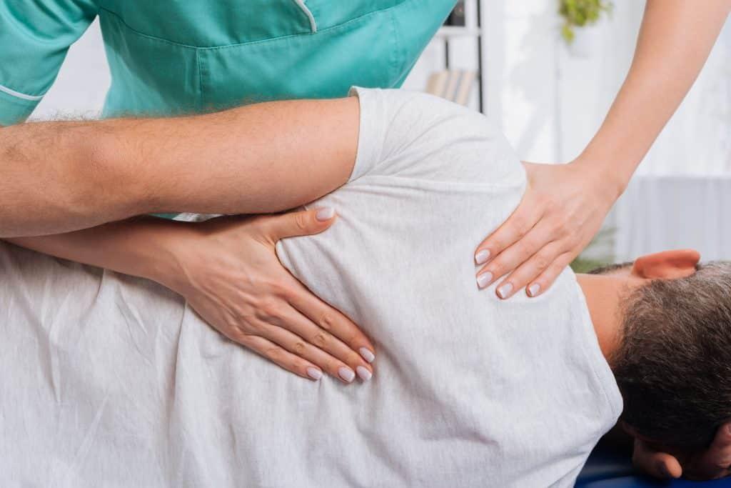 Quiropraxista com as mãos nas costas do paciente