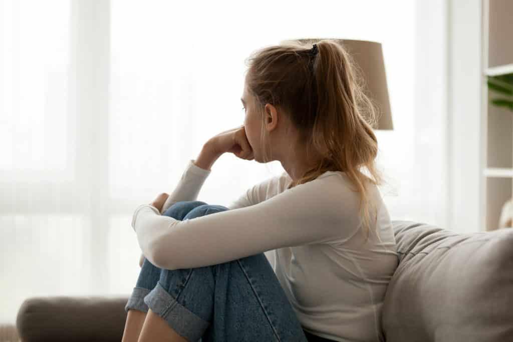 Mulher sentada no sofá e olhando para janela.