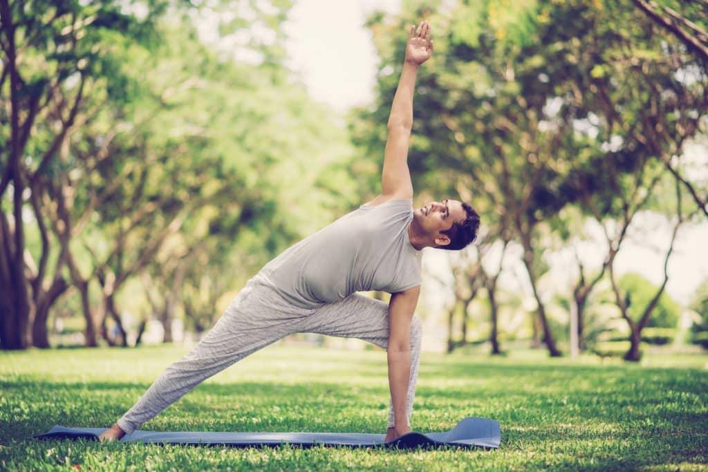 Homem branco fazendo a postura do triângulo estendido.