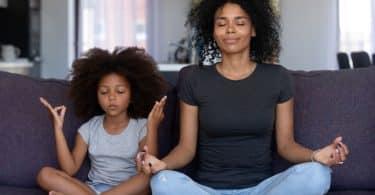 Mulher adulta e menina sentadas em sofá. Elas praticam meditação.