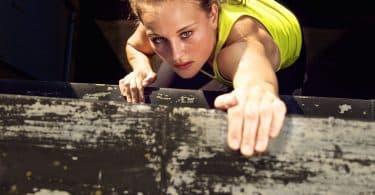Mulher determinada escalando uma parede de madeira