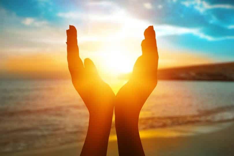 Mãos ao redor do sol na praia.