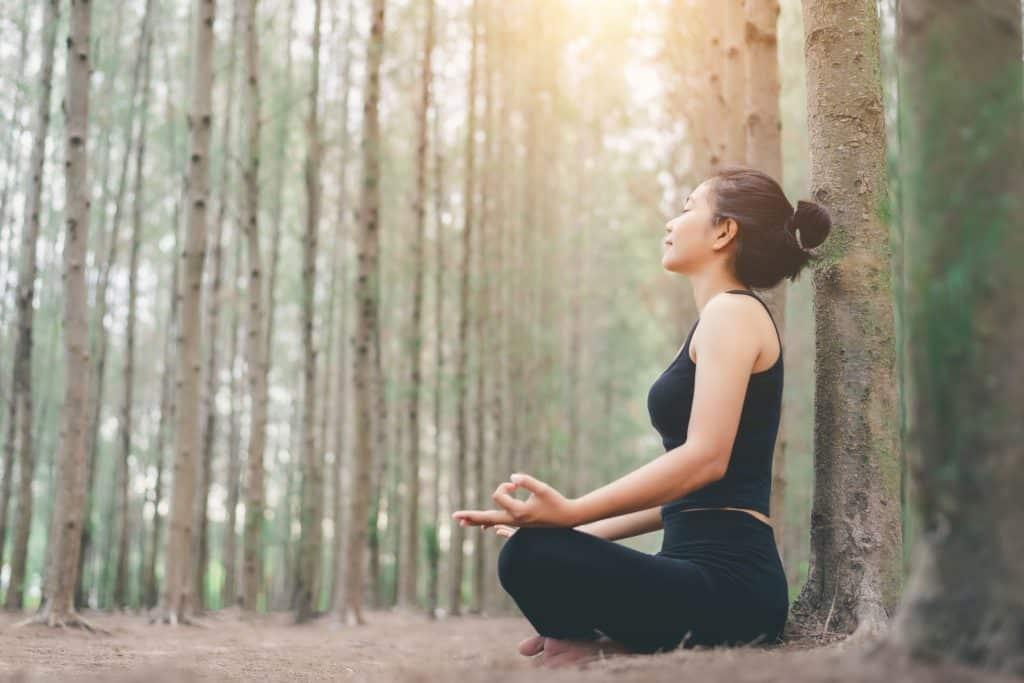 Mulher sentada em uma floresta meditando.