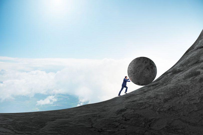 Homem empurrando uma grande pedra para o topo de montanha.