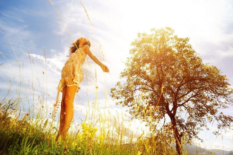 Mulher com os braços abertos e cabeça erguida. O cenário é externo, de vegetação e solar.