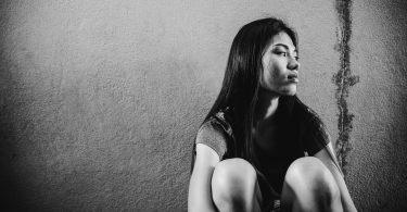 Mulher asiática sentada no chão com expressão triste.