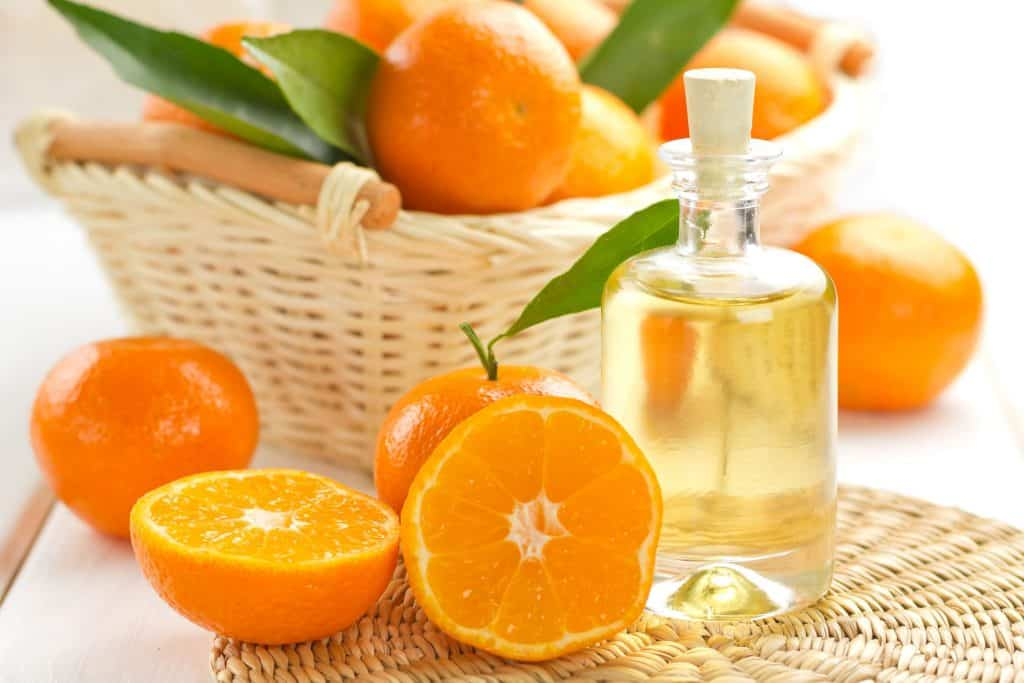 Óleo de laranja com laranjas cortadas ao redor