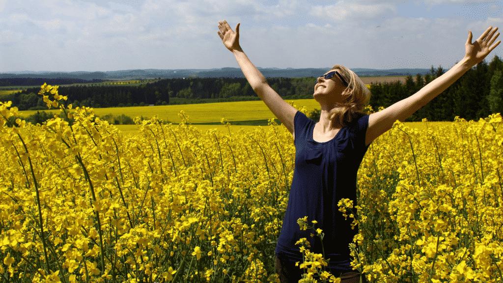 Mulher com os braços erguidos em um campo de flores agradecendo