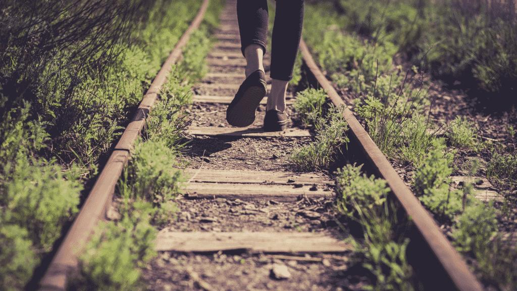 Pessoa caminhando sobre os trilhos do trem desativados