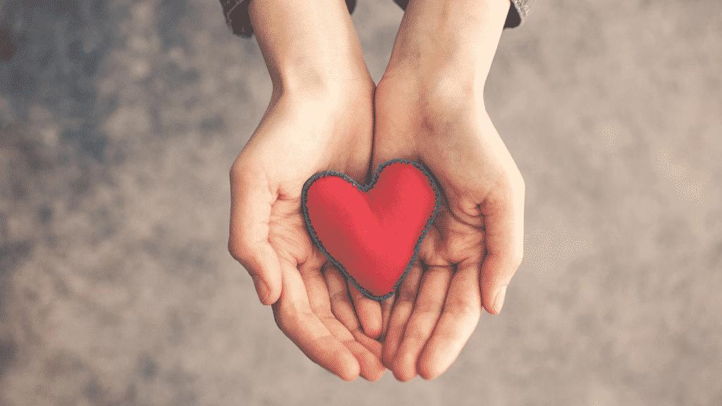 Mãos segurando um coração de costura
