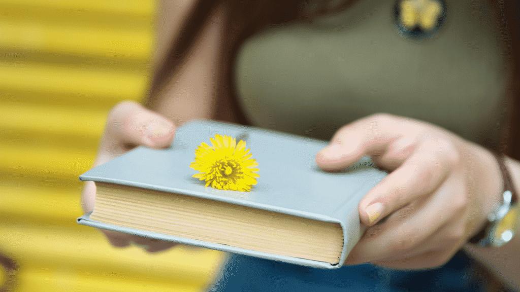 Mulher oferecendo um livro com uma flor em cima