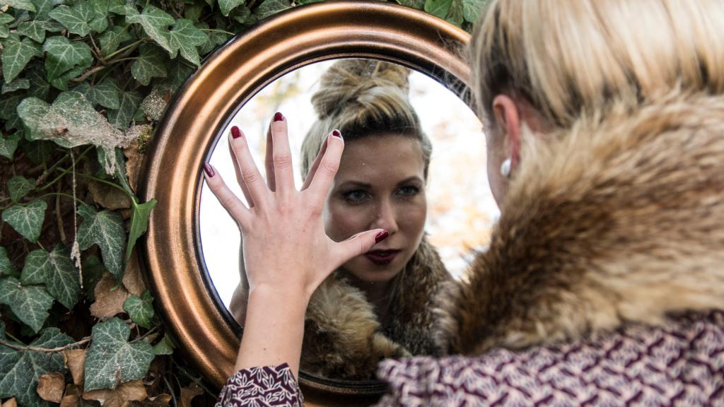 Mulher se olhando com a mão no espelho