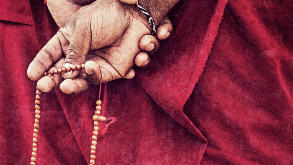 Homem budista segurando colar de contas