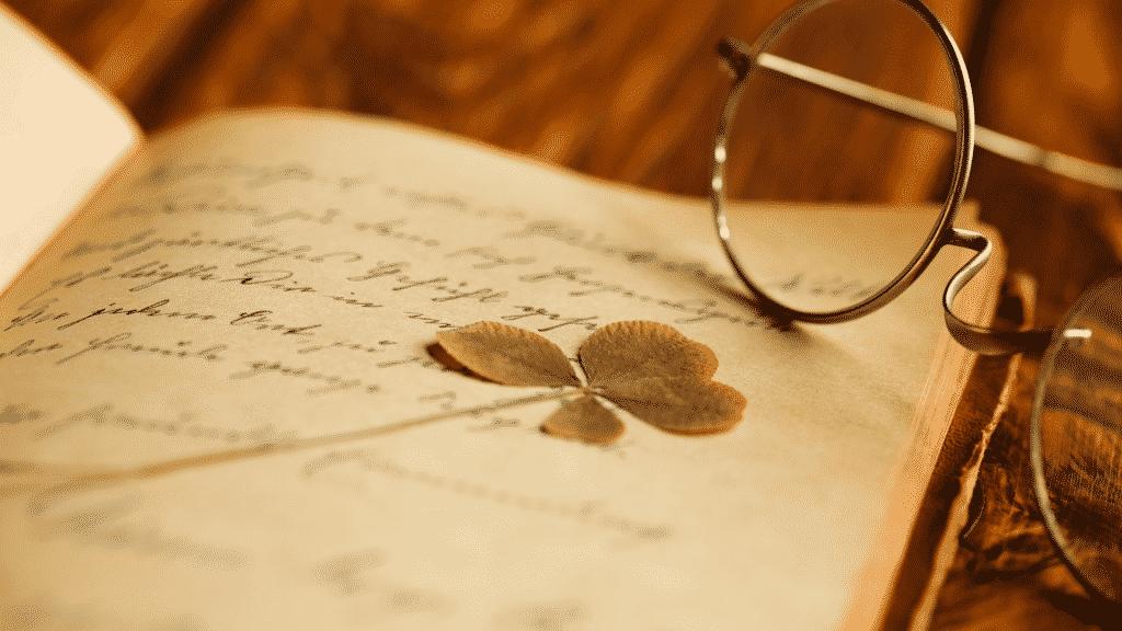 Paginas abertas de um livro de poesias com um óculos sobre ele