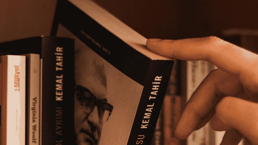 Pessoa escolhendo livro da prateleira