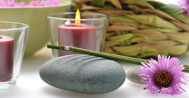 Imagem de dois incensos de lavanda acesos disposto sobre uma pedra cinza. Ao lado um como de cristal com uma vela na cor rosa dentro. A vela está acesa. Sobre a esa e ao lado do incenso uma flor também na cor rosa.