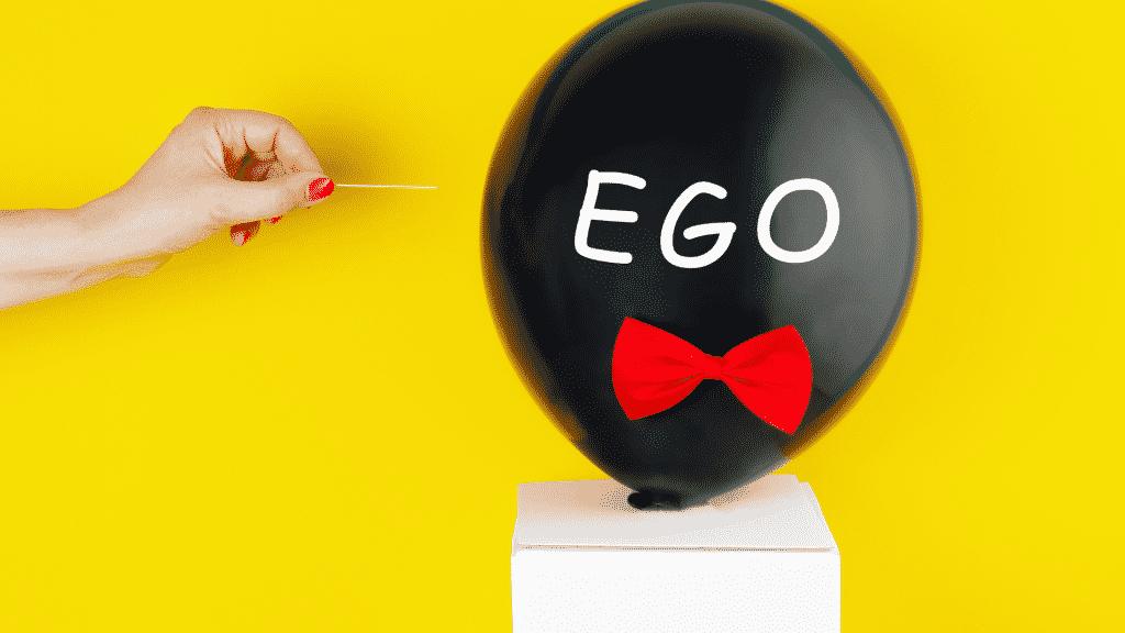"""Mulher prestes a estourar um balão preto escrito """"ego"""" com palito de dente"""