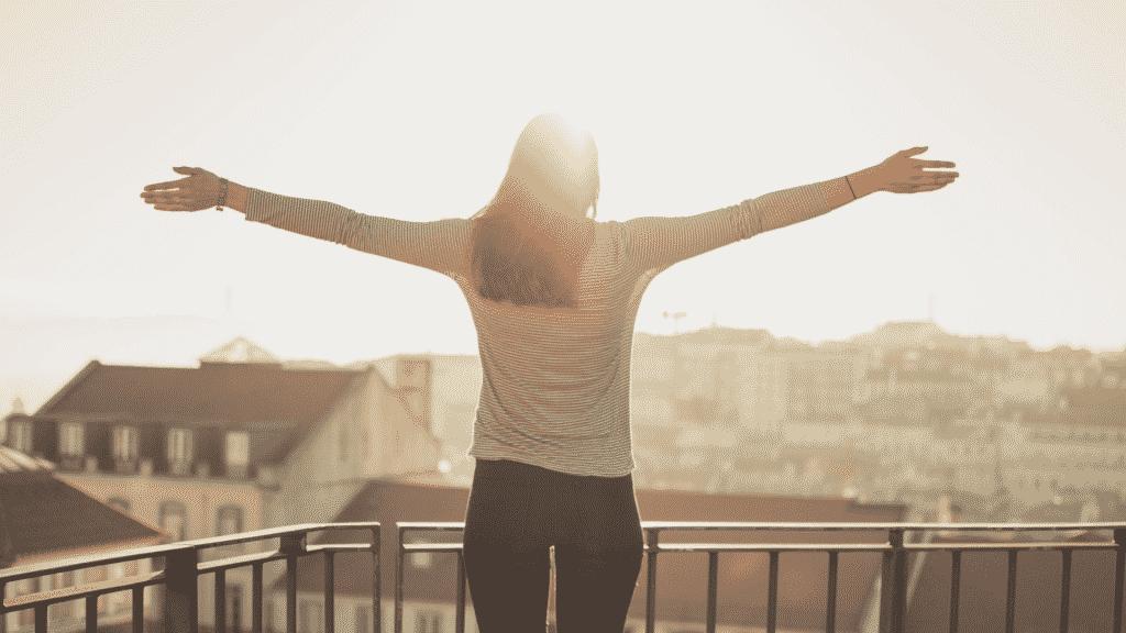 Mulher de costas com os braços abertos na varando durante por do sol