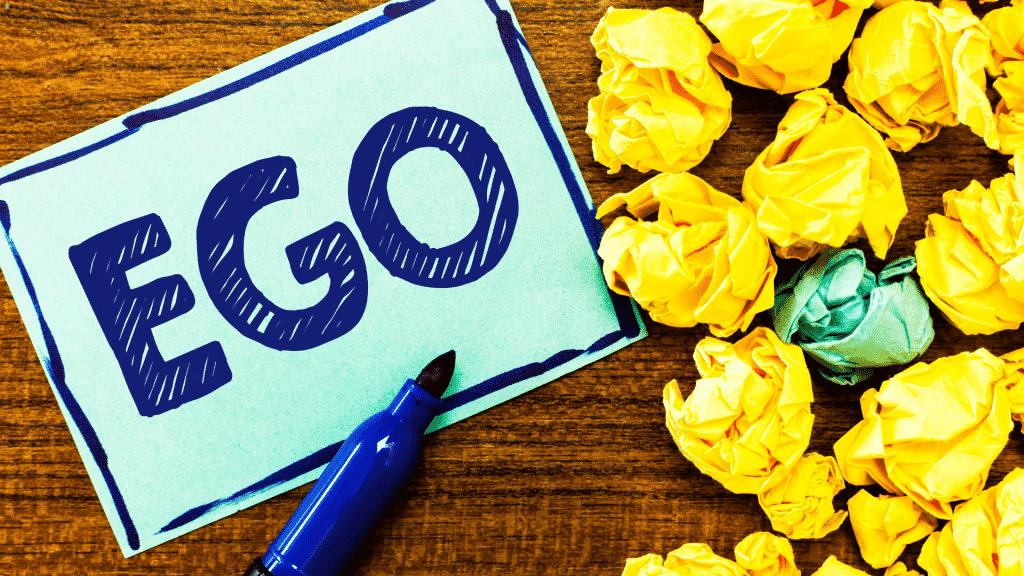 """Papel escrito """"ego"""" de canetinha azul com a caneta ao lado e vários papeis amassados"""